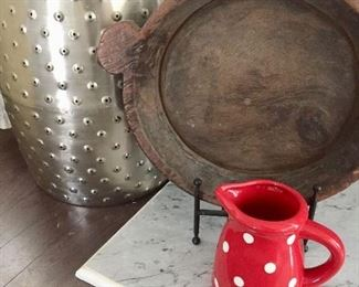 Fun silver Chinese garden seat looks lovely paired with rustic cooking pot and bright polka-dot pitcher.  (Pitcher sold)