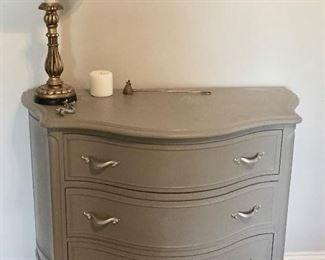 Painted antique small dresser with table lamp.
