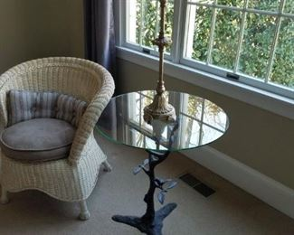wicker chair with glass-top & metal base table (bird/tree branch detail on base)