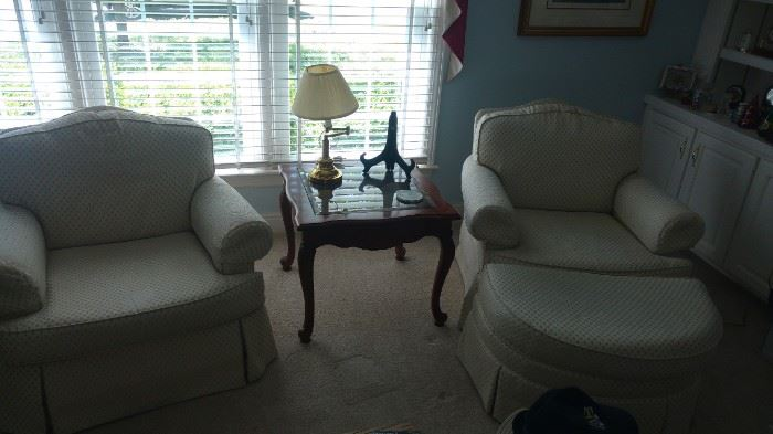 pair of swivel chairs and one ottoman