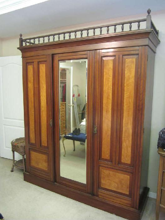 Mahogany Armoire, likely made in England.   Late Eastlake 1890s-Early 1900s. Beautiful. Three doors.  One is a closet, the other two open and have wonderful pull out drawers.