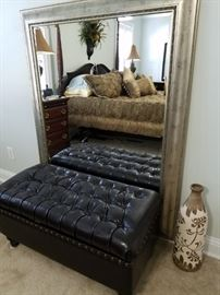 Tufted pleather storage chest. Large metal framed mirror, pottery vase.