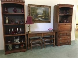 Two bookcases.  The center piece of furniture is a sofa table with two stools.