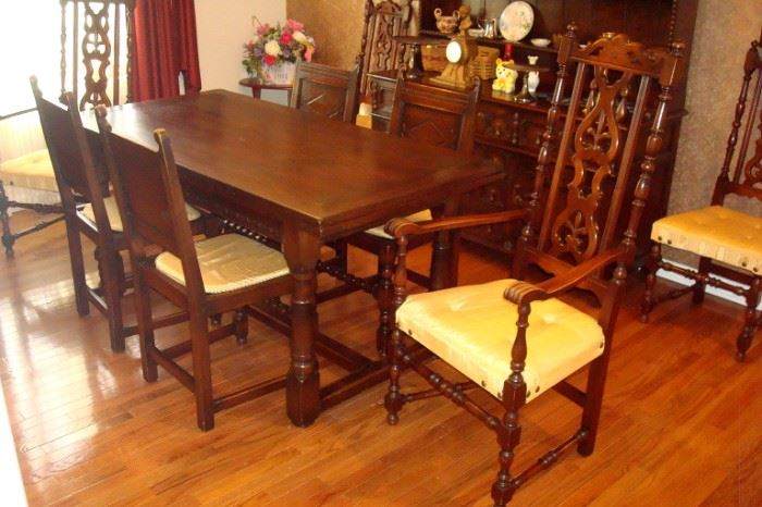 Spanish/Flemish influence antique dining suite with dark oak table which has hidden leaves, eight chairs as shown, an open cupboard and a high boy china chest. C-1870.