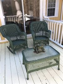 Two green wicker chairs, table and frog planter
