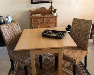 Two rattan straight back chairs and small table. Woven rug