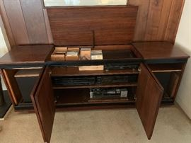 Mid Century Modern hi-fi stereo cabinet with one lift top cabinet and three cabinet doors below on the front