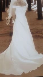 Beautiful boxed wedding gown with lace detail. Ladies size 4.