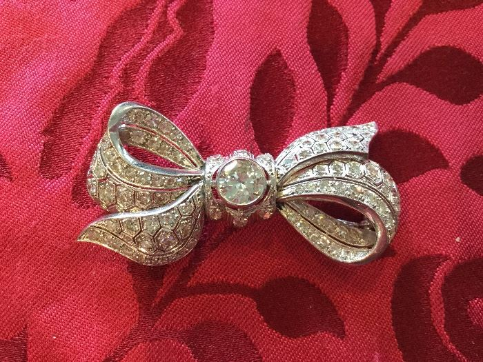 Platinum Bow Knot brooch pin, set with a round cut diamond of 150 points and approximately 85 round cut diamonds of .04 points $11,000