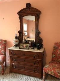 Antique ornate Victorian walnut dresser with marble top and mirror.
