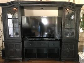 Entertainment Center - $300   This entertainment Center has two 26 inch wide side cabinets with glass doors.  Each cabinet has 2 glass shelves and a 3 way light, which is controlled by tapping the hinge on the outside of the door.     The 3rd piece is the bridge across the top.  When the 3 pieces are attached, the bridge can slide and adjust to fit up to an 80 inch TV.                                          The black console is a separate 60 inch piece.  It has 3 drawers and 3 open compartments.  Id was not an original piece of the entertainment center, but matches nicely.