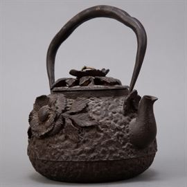 A lovely well made iron teapot decorated with applied flowers. Inlay in handle. Dimensions: Height (including handle): 9 in x width: 7 in x depth: 5 in.