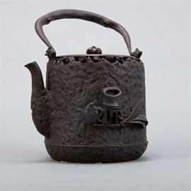 Japanese tetsubin iron kettle with an iron lid attributed to Ryubundo. Both sides have designs in high relief--one of flowers and the other of a tea scene. The kettle has a signature along the underside of the lid. Dimensions: Height (including handle): 9 1/2 in x width: 6 in x depth: 5 1/4 in.