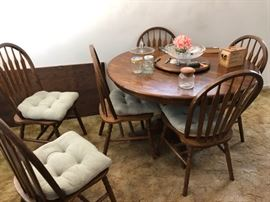 Round dining table with expandable leaf piece and 6 chairs