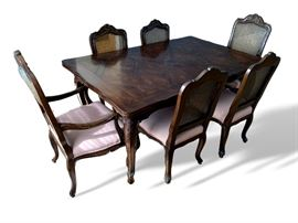 Solid wood dining room table and chairs as shown. Table has slide out leaves on each side.  Shows wear - cane chair backs show damage.  Table measures 67 inches long by 44 inches wide.
