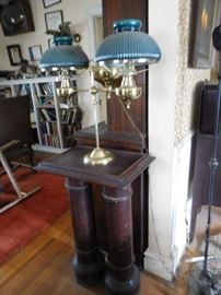 green  lamp  on  a   double  pedestal ,lots  of  books