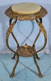 283a  Brass Victorian pedestal with onyx top and ladies heads on legs, 32 in. T, 18 in. Dia.