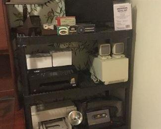 Light, Dell monitor, printer, Ink white boxes, speakers, printer, vintage VHS camera, paper Shredder