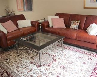 Two Piece Like New Leather Sofa Set with Handmade Rug 8×10 and Metal & Glass Coffee Table with Accent Pillows