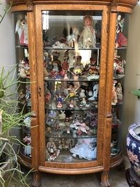 Antique china cabinet filled with dolls from around the world