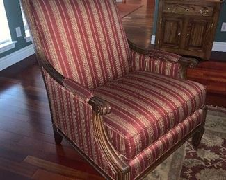 Upholstered armchair with carved wooden trim