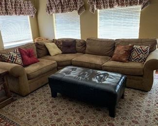 Pottery Barn Upholstered L-shaped sectional sofa, coordinating throw pillows, and large leather tufted ottoman / coffee table