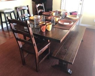 Rustic trestle style farmhouse  dining table with bench seating, and three matching dining chairs