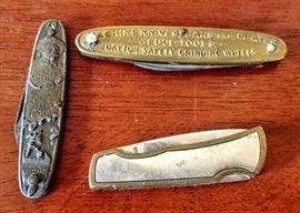 vintage pocket knives:  Buffalo Bill Cody, machinery ad piece, & metal