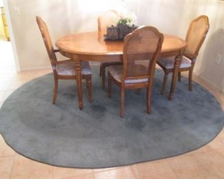 """Dining Room Table/4-Chairs by Thomasville with          2-16"""" Leaves, 44"""" X 66"""".  Chairs have Cane Backs and Upholstered Seats.  Oval Blue Area Rug, 7' X 9'"""