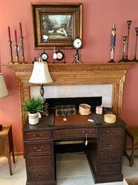 Kneehole desk; table lamp; clocks, candlesticks; framed art of sheep