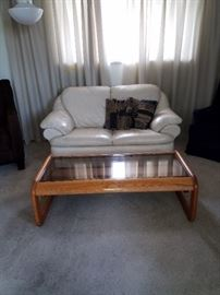 Leather loveseat and glass top coffee table