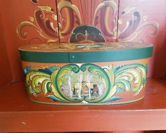 Rosemaling oval box with lid on bench.