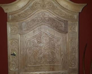 Unpainted carved wooden wall cabinet, single door with lock.