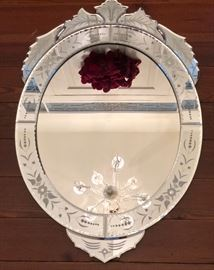 Venetian style foliate glass wall mirror. Reversed etched, floriform crest over applied beveled embellishments.
