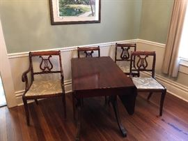 Mahogany dropleaf Duncan Phyfe table and 4 upholstered chairs. Three straight, one master.  Brass feet. Absolutely beautiful condition!