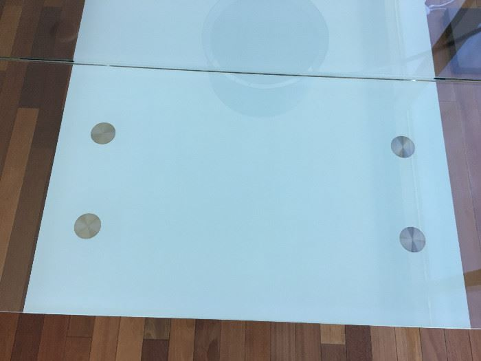 Looking down on table, glass leaves at each end can be lowered and stored under the table with a lever.