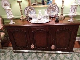 Vintage Baker French sideboard, with silverware drawers, pair of French porcelain lidded urns, pair of vintage brass candlestick lamps, pair of cloisonne vases on stands, pair of English silverplated shell servers, trio of crystal decanters on silverplated tray.
