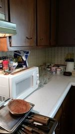 Countertop microwave, kitchen knives, bakeware, glassware, coffee cups