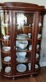 Unusual display case with curved glass sides and wooden shelves. Excellent condition.
