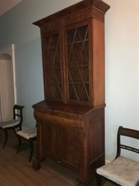 2nd Quarter 19c mahogany and mahogany veneer secretary w/ glazed doors above blind doors and scrolled stiles in front.   Similar to those done by J. & J. W. Meeks and others on the East Coast.