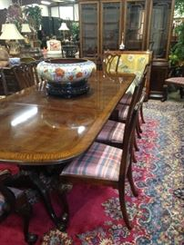 This elegant dining table comfortably seats 12 people. It has an extra leaf not shown and two armed host chairs.