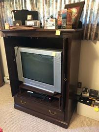 entertainment center, tv, clocks, VHS tapes