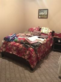 Bed with matching dresser and nightstand and lots of linens