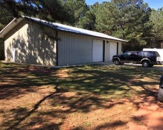 Like-New 40' x 60' Metal Building with (2) Overhead doors, side entry door and concrete floor.  Property also has concrete pad for motor home with electric and water well.