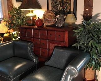 Pair of green leather chairs, gorgeous Bassett cabinet, silk plants, pottery, tribal masks, handmade colorful baskets, brass lamp