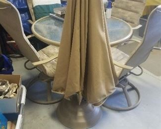 Patio table and 4 swivel/rocker chairs and covers with umbrella
