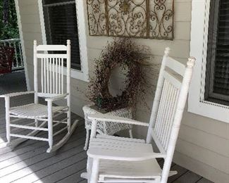 Have a seat on the front porch in these white rockers, also wicker table and metal wall art