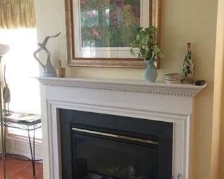 wall art, large candle, brass container to the right of the fireplace