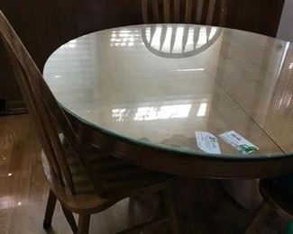 round oak table and 4 chairs.  Glass top. Also nice Oak dining table with leaf and 6 chairs