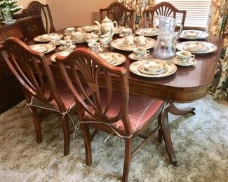 Antique dining room table and chairs and Johnson Brothers Friendly Village dinnerware. There are 13 different plates depicting covered bridges and more.